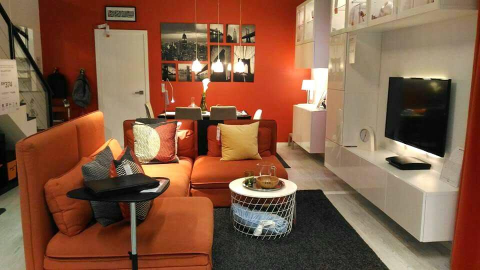 Ruang tamu moden dengan kabinet tv putih dan sofa oren