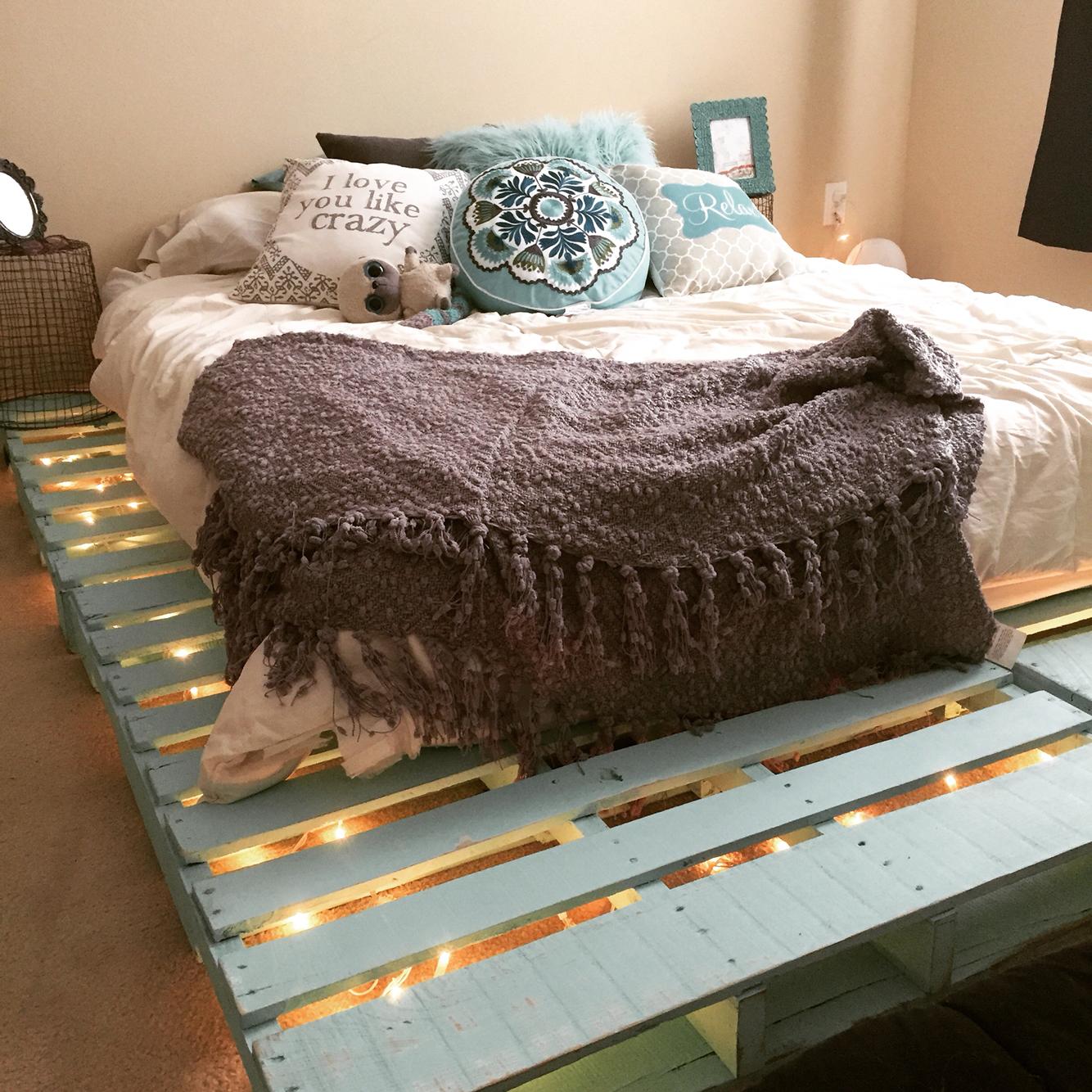 Pastel turquoise lembu rangka katil kayu pallet diterangi oleh lampu